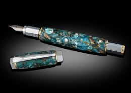 Fountain pen with magnetic cap, chrome and gold, sea shells cast in aqua resin. Iridium pen nib and uses either an ink cartridge or converter pump. Pen can also be made as a rollerball.