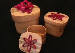 "Set of 3 ambrosia maple nesting lidded boxes with red dyed pine bows. Large; 5"" long, 4.25"" wide, 3.8"" high. Medium; 3.75"" long, 3.25"" wide, 3"" high. Small; 3.2"" long, 2.6"" wide, 2.2"" high. Available."