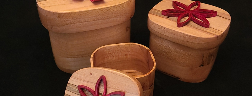 """Set of 3 ambrosia maple nesting lidded boxes with red dyed pine bows. Large; 5"""" long, 4.25"""" wide, 3.8"""" high. Medium; 3.75"""" long, 3.25"""" wide, 3"""" high. Small; 3.2"""" long, 2.6"""" wide, 2.2"""" high. Available."""