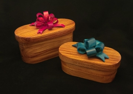 "Canary wood lidded boxes with dyed pine bows. Left with red bow; 7.75"" long, 4"" wide, 4"" high. (measurement without bow included) Right with teal bow; 6.5"" long, 3.25"" wide, 2.5"" high measurement without bow included). Available"