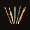 eft to right; twist ballpoint, music motif, pewter, navy resin; twist ballpoint, art deco style, chrome with gold accents, clear box elder burl; twist ballpoint, SW motif, pewter with turquoise inlay, tru-stone turquoise with black veining; twist ballpoint with fly fishing motif, pewter, navy/gray/light blue resin; rollerball with removable magnetic cap that also fits on end cap, apple tree twigs.