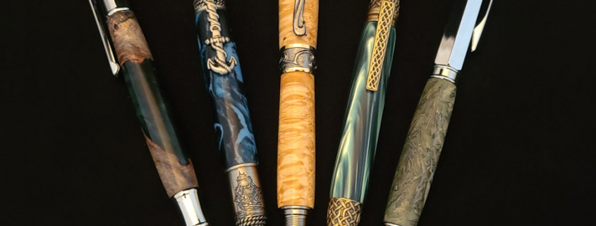 Left to right; twist ballpoint, chrome, dark green resin with maple burl; twist ballpoint, pewter, nautical motif, navy/light blue swirled resin; rollerball art deco style, gun metal with gold accents, top cap also screws on end cap, box elder burl; twist ballpoint, antique brass finish, celtic motif, dark green resin; rollerball, chrome withmagnetic cap that fits on both ends, shredded money imbedded in resin.