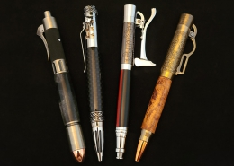 """Left to right; ballpoint click pen, pewter with copper tip, revolver motif, steel gray resin; ballpoint click pen, chrome, gear shift motif, carbon fibre; ballpoint click pen, chrome, firefighter motif, axe handle is the """"click"""", black acrylic with thin red line; ballpoint click pen, antique brass finish, old fashioned lever action, maple burl."""