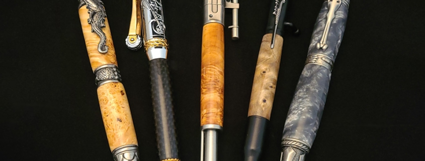 Left to right; twist ballpoint, pewter, dragon motif, clear box elder; twist ballpoint, chrome with gold plate, motorcycle motif, carbon fibre; click ballpoint, rifle motif, pewter, clear box elder burl; click ballpoint, 35mm bullet motif, black enamel and chrome, maple burl; twist ballpoint, pewter, skull motif, grey resin