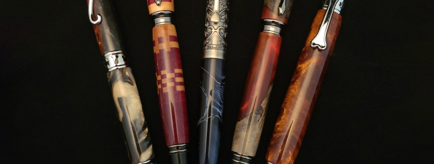 Left to right; twist ballpoint, chrome, cat motif, rust/white/grey resin; rollerball with magnetic cap, gun metal, purple heart and maple; twist ballpoint, pewter with clear crystals, navy swirl resin; fountain pen with magnetic cap, red resin with maple burl; click ballpoint, chrome, dog motif, molten bronze resin
