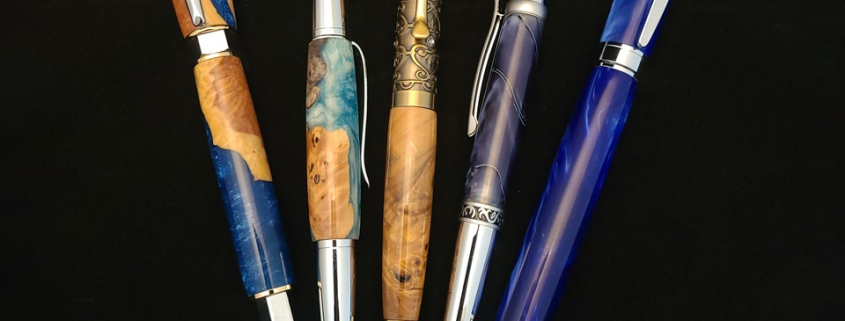 Left to right; rollerball with magnetic cap, chrome and gold plate, blue resin with burl; twist ballpoint, chrome, aqua resin with burl; twist ballpoint, brass with crystals, clear box elder burl; twist ballpoint, chrome and satin chrome, navy swirl resin; fountain pen with magnetic cap, chrome, bright blue resin
