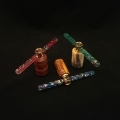 """Small wand kaleidoscopes; left to right; blood wood with red wand, body 3.25"""" long, 1.25"""" wide, wand 6"""" long; marblewood with blue wand, body 3.25: long, 1.25"""" wide, wand 6"""" long; spalted tamarind with green wand, 3.25"""" long, 1.25"""" wide, wand 6"""" long."""