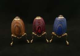 "Egg shaped teleidocopes and kaleidoscopes; left to right; teleidoscope in brown ""mystery"" wood, 2.75"" tall, gold plated stand (included) 1.5"" tall, 2.5"" wide; kaleidoscope in red and blue laminated wood, 3"" tall, gold plated stand (included) 1.5"" tall, 2.5"" wide; teleidoscope in blue and gray laminated wood, 3"" tall, gold plated stand, 1.5"" tall, 2.5"" wide"