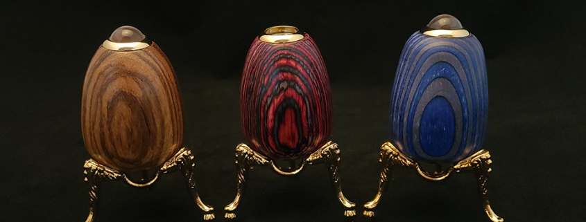 """Egg shaped teleidocopes and kaleidoscopes; left to right; teleidoscope in brown """"mystery"""" wood, 2.75"""" tall, gold plated stand (included) 1.5"""" tall, 2.5"""" wide; kaleidoscope in red and blue laminated wood, 3"""" tall, gold plated stand (included) 1.5"""" tall, 2.5"""" wide; teleidoscope in blue and gray laminated wood, 3"""" tall, gold plated stand, 1.5"""" tall, 2.5"""" wide"""