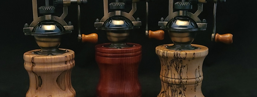 """Antique style pepper mills with adjustable grind; left to right; ambrosia maple 7"""" tall, 3.25"""" wide; bloodwood, 7"""" tall, 3.25"""" wide; spalted tamarind, 7.25"""" tall, 3"""" wide"""