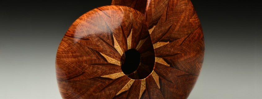 """Canary wood (pinwheel design is not an inlay but is the sapwood); 9"""" long, 9"""" high, 6.5Canary wood (pinwheel design is not an inlay but is the sapwood); 9"""" long, 9"""" high, 6.5"""" deep. Available"""" deep. Available"""